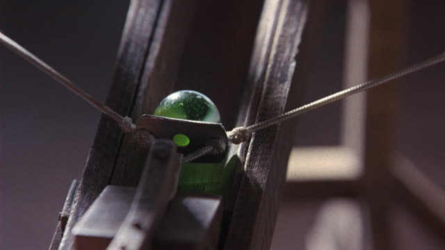 vidéos et rushes de close angle of a catapult with a green marble or ball cocked back. the trigger releases, and the ball flies off. toys. - fronde