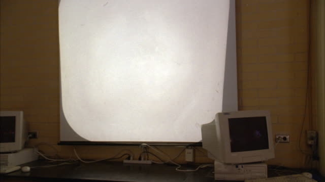 medium angle of an overhead projector screen with two computer monitors next to it. - overhead projector stock videos & royalty-free footage