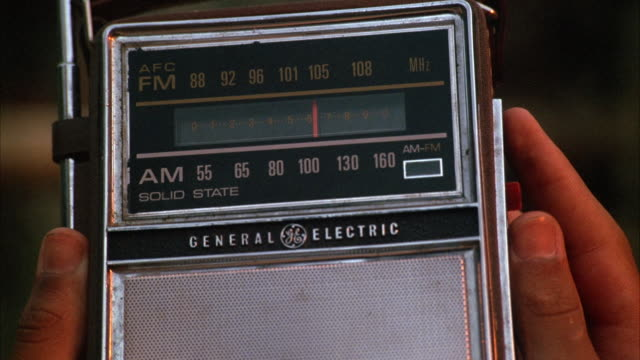 close angle, see hands holding portable am/fm general electric radio. see dial moving  left to right, right to left. - general electric stock videos and b-roll footage