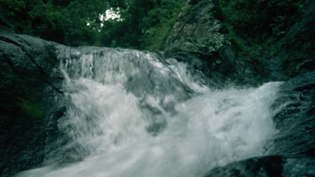 medium angle of waterfall over rocks. - flowing water stock videos & royalty-free footage
