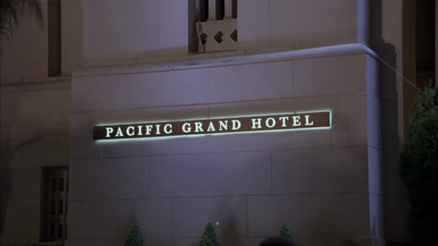 MEDIUM ANGLE OF PACIFIC GRAND HOTEL SIGN ILLUMINATED ON WALL OF PARK PLACE HOTEL.