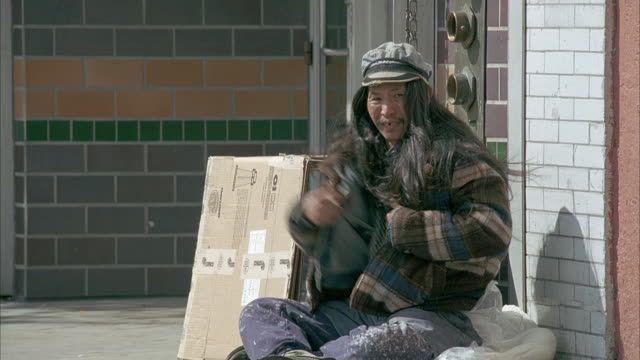 medium angle of homeless asian man sitting on sidewalk. - tramp stock videos & royalty-free footage