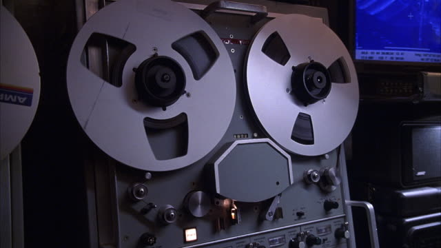 close angle of a reel to reel recorder or playback machine. - 1998 stock-videos und b-roll-filmmaterial