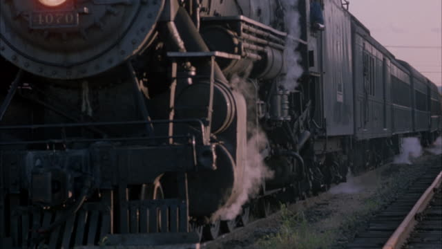 close angle shot of steam train slowly moving to camera down track.  focuses in on turning wheel gears and steam flowing from beneath. neg cut. - steam train stock videos & royalty-free footage