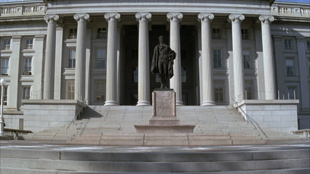 vidéos et rushes de medium angle of front of united states treasury building with statue of alexander hamilton in front. pov starts low to ground and moves up to get different angle. - trésor public