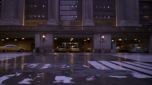 wide angle of grand central station. see taxis parked in front. pov is from across the street. - grand central station manhattan stock videos & royalty-free footage