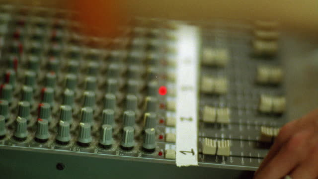 CLOSE ANGLE OF AUDIO OR SOUND BOARD IN RADIO STATION OR PRODUCTION STUDIO.