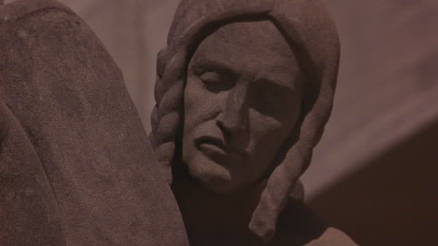 medium angle of stone statue of woman with eyes closed. statue is feature of louisiana state capitol building. - kapitol von louisiana stock-videos und b-roll-filmmaterial