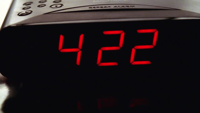CLOSE ANGLE OF DIGITAL ALARM CLOCK ON TOP OF STACK OF MAGAZINES. CLOCK IS BLACK WITH RED NUMBERS, TIME IS 4:22. INSERT. LIGHT IN BACKGROUND TURNS ON AT END.
