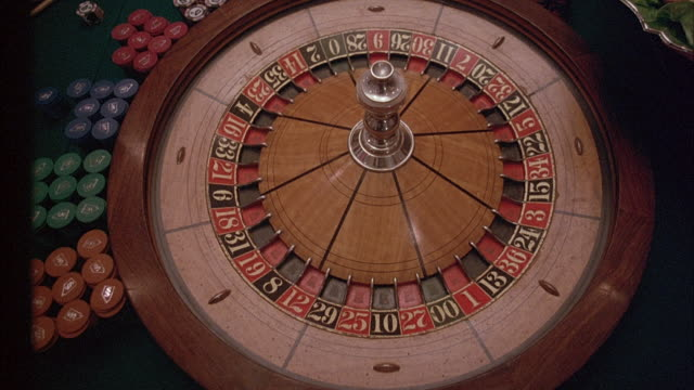 medium high angle down of roulette wheel in casino. see hand spin wheel and toss ball around rim. see stacks of casino chips on left. - casino stock videos & royalty-free footage