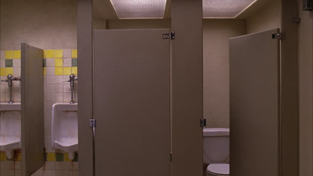 wide angle of stalls and urinals in a men's public restroom. one stall is closed, another is half open and empty. bathroom appears clean. could be rest area, office building, or restaurant. - 小便器点の映像素材/bロール