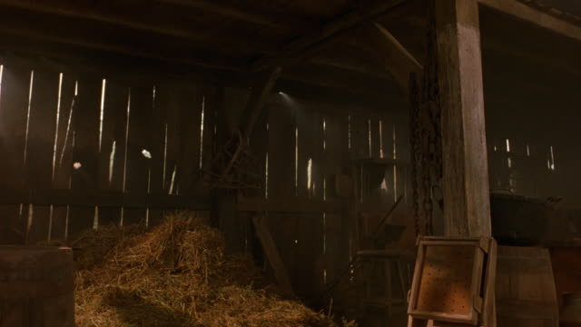 medium angle of barn. see haystack in foreground. see wooden barrels in foreground. - haystack stock videos & royalty-free footage