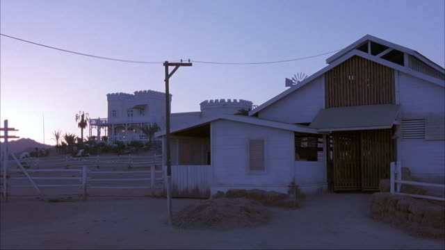 medium angle of white wooden barn in small rural or desert town. see stacks of hay in front and electrical wires running above barn. see upper class castle styled, two story house with large balcony in background. - hay background stock videos & royalty-free footage