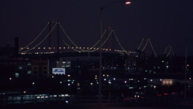 wide angle of lit bay bridge at night over south of market area of san francisco. street lamps in foreground. - san francisco oakland bay bridge stock videos and b-roll footage