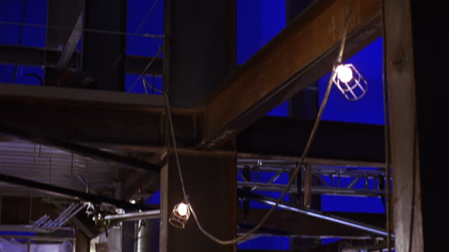 PAN RIGHT TO LEFT, UP AND DOWN OF GIRDER FRAME FOR BUILDING UNDER CONSTRUCTION.  BLUE LIGHTS OR BLUESCREEN BACKGROUND. EXPOSED CONDUITS, SAFETY NETTING.