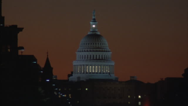 ESTABLISHED MEDIUM ANGLE OF CAPITOL BUILDING. SKY HAS RED AND ORANGE TINT. OUTLINE OF OTHER BUILDINGS SURROUND CAPITOL.