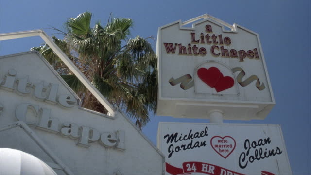 up angle of sign that reads little white wedding chapel. pans down at end. - chapel stock videos & royalty-free footage
