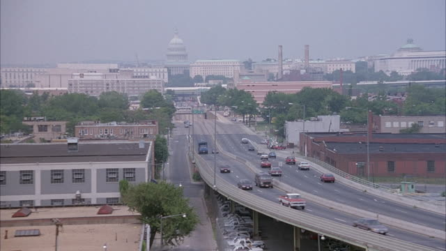 AERIAL OF HIGHWAY LEADING INTO CITY WITH CAPITOL BUILDING IN BACKGROUND.