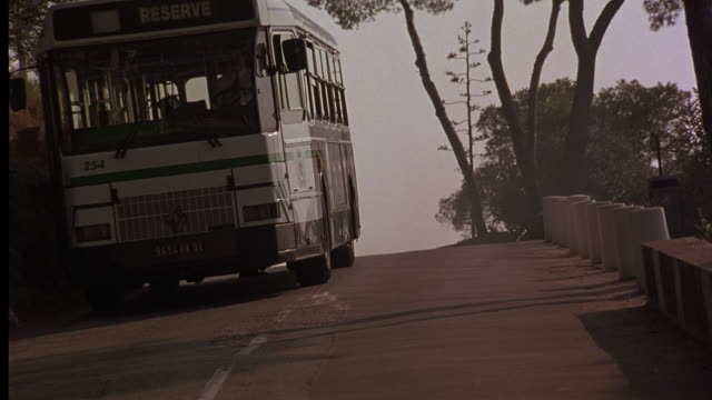 UP ANGLE OF CITY BUS DRIVING ON NARROW COUNTRY ROAD.
