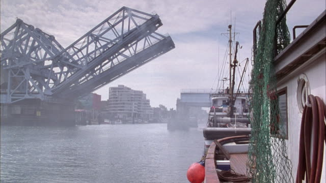 vídeos de stock, filmes e b-roll de medium angle of river and drawbridge with boat in right foreground, pov could be on boat. bridge raises slightly upwards - drawbridge