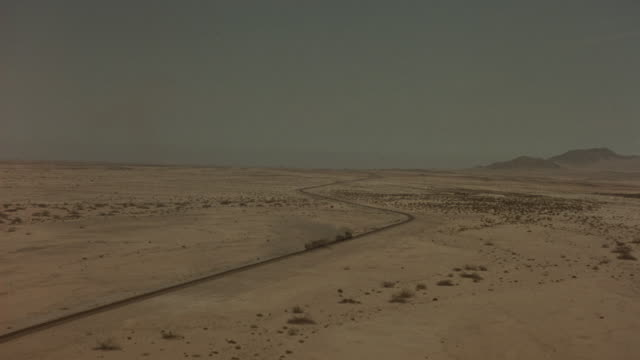 aerial of train slowly chugging along a track weaving through the desert. see black smoke rising from the pipe of the train. bushes dot the barren landscape. - locomotive stock-videos und b-roll-filmmaterial