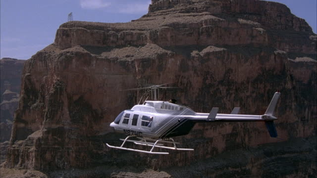 MEDIUM ANGLE OF HELICOPTER FLYING IN INTERIOR OF GRAND CANYON.