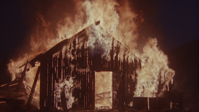 medium angle of small barn or storage shed on fire. see flames consuming slats of wood. - 抜け殻点の映像素材/bロール