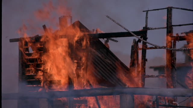 medium angle of orange flames of fire burning wooden beams of frame of house or shack. roof of house collapses as flames burn through wooden beams. - collapsing stock videos and b-roll footage