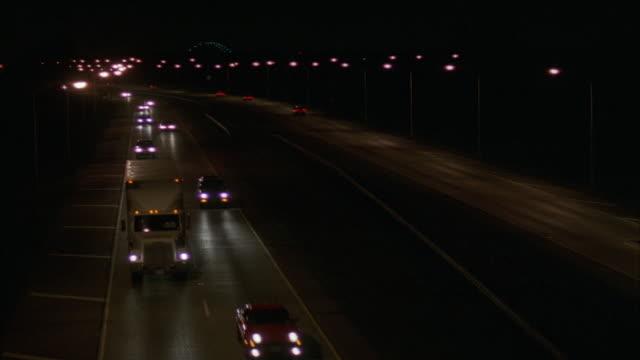 high angle down of freeway with two way traffic. camera tracks down silver sedan that exits frame to bottom. - 1995年点の映像素材/bロール