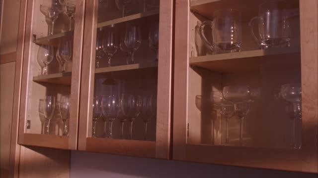 vídeos de stock e filmes b-roll de medium angle of wood cabinets in kitchen. refrigerator visible in background. glassware on shelves. - armário
