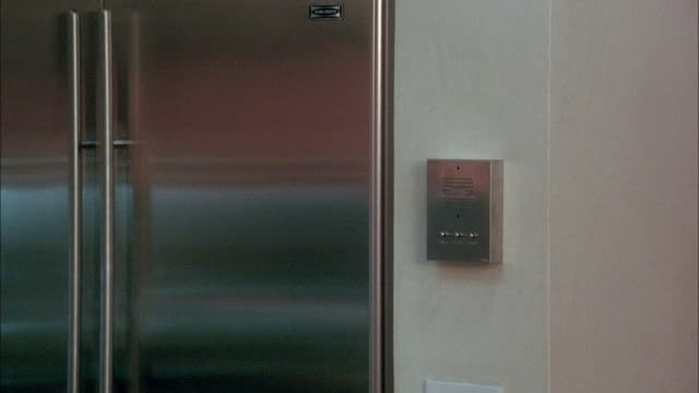 est medium angle of intercom next to metal refrigerator doors. - frigorifero video stock e b–roll