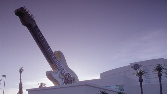 established medium angle of hard rock hotel with giant guitar with sign on left. - ハードロックカフェ点の映像素材/bロール