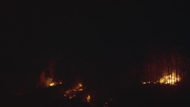 WIDE ANGLE OF FOREST FIRE RAGING ON HILLSIDE.