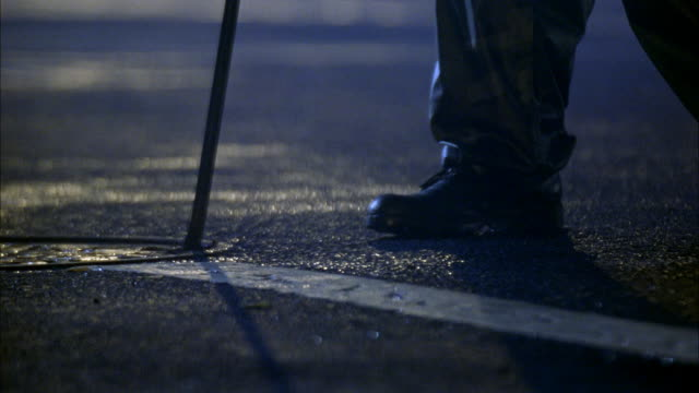 CLOSE ANGLE OF SOLDIER'S FEET AS HE STANDS NEAR MANHOLE COVER.