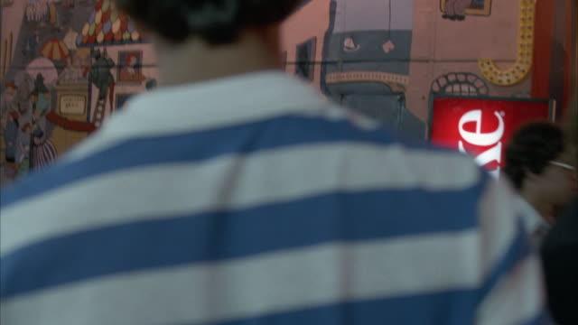 vídeos y material grabado en eventos de stock de medium angle moving pov through crowd at carnival. see coke vending machine on right. lights flashing and carnival rides. - coca cola
