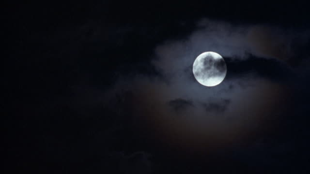 up angle of full moon in sky, clouds move from right to left to partially obscure view. - 1990 stock videos & royalty-free footage