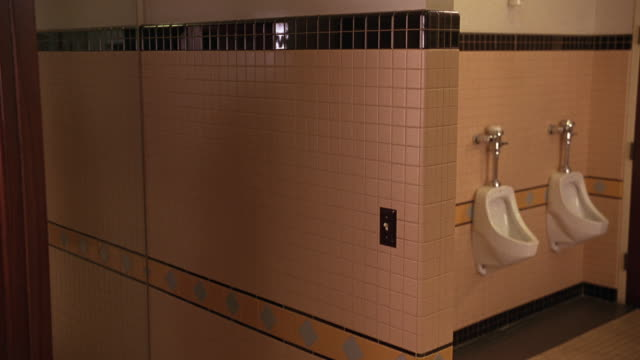 medium angle of men's restroom. urinals visible to right. tile walls and floor. - 小便器点の映像素材/bロール