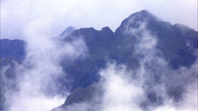 wide angle of clouds moving up mountain peak. - ecuador stock videos & royalty-free footage