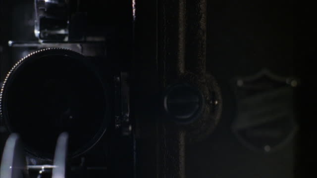 CLOSE ANGLE OF MOVIE PROJECTOR FACING CAMERA WITH LENS ON RIGHT. EVERYTHING IS OFF.