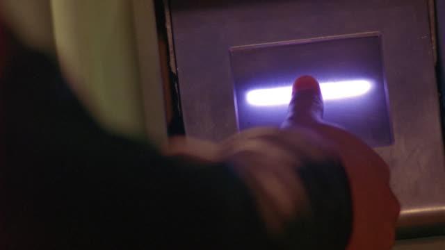 medium angle of stunt fingerprinting. see green neon light, or scan light. futuristic. lasers. - fingerabdruck stock-videos und b-roll-filmmaterial