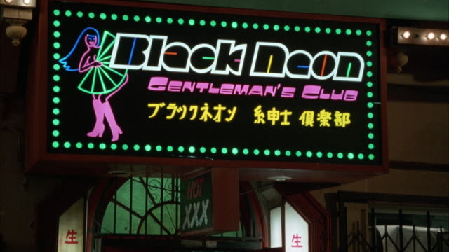 MEDIUM ANGLE OF SIGN THAT READS BLACK NEON GENTLEMAN'S CLUB. PANS DOWN AT END OF SHOT TO ENTRANCE.
