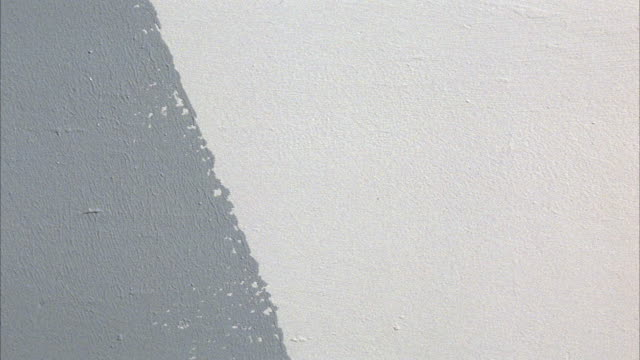 close angle of white wall. hand comes in with paint roller, painting wall gray. - paint roller stock videos & royalty-free footage