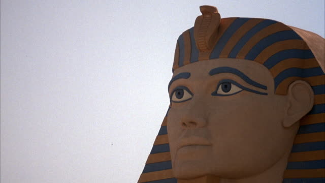 MEDIUM ANGLE OF HEAD OF SPHINX FIGURE FACING LEFT AT LUXOR HOTEL. JET FLIES TO RIGHT IN BACKGROUND.