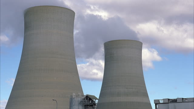 wide angle of nuclear power plant. see pair of concrete cooling towers with steam rising from top. gray structure visible on frame right. blue sky with white clouds in background. - kernenergie stock-videos und b-roll-filmmaterial