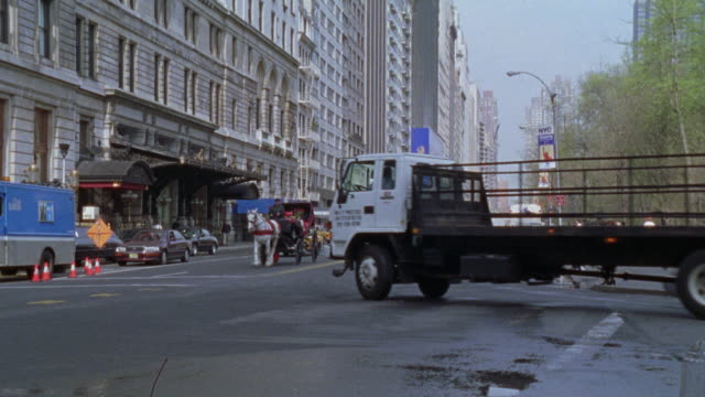 pan right to left of the plaza hotel next to central park as a limo and a horse drawn carriage drive by. - 2001 stock videos and b-roll footage