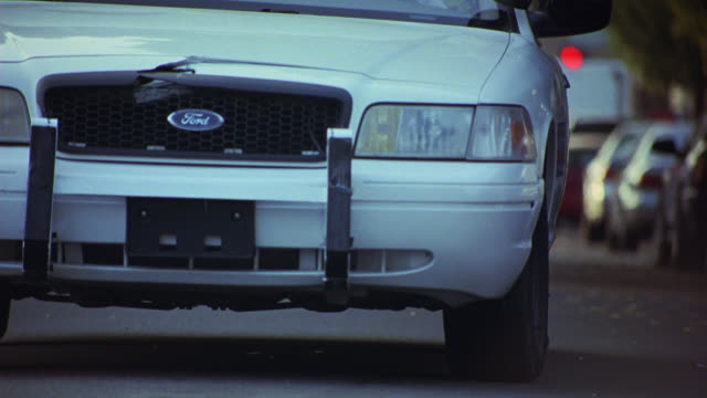 medium angle of front end of ford police car. car accelerates and then brakes or stops quickly. - brake stock videos & royalty-free footage