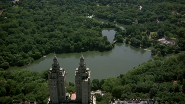 aerial. moving shot of central park. see buildings, pond, and trees. - central park manhattan stock videos & royalty-free footage