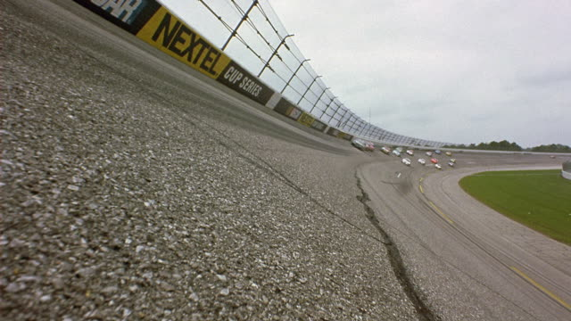 WIDE ANGLE OF NASCAR RACETRACK, FENCE, BARRIERS. RACE CARS SPEED TOWARD CAMERA, PASSING ON BOTH SIDES.
