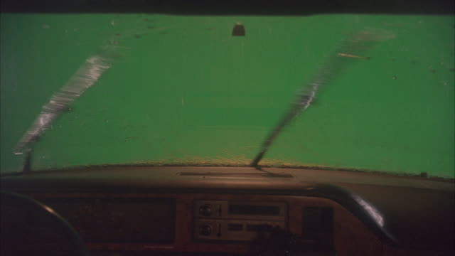 vídeos de stock e filmes b-roll de medium angle of wiper blades moving back and forth. pov from inside of car. green screen in background. rain falling on windshield. - para brisas