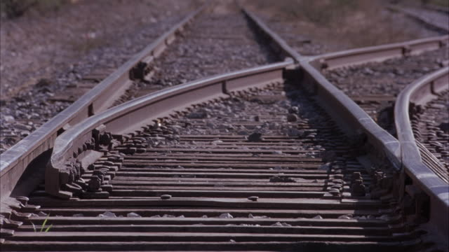 CLOSE ANGLE OF RAILROAD TRACK SWITCH. SEE SWITCHER CHANGE TWICE BETWEEN TWO DIFFERENT RAILROAD ROUTES. SEE SMALL ROCKS AROUND TRACKS.